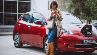 kobieta ladujaca samochod elektryczny na stacji benzynowej